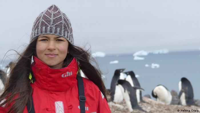 A teenage girl dressed in warm clothes, penguins in the background