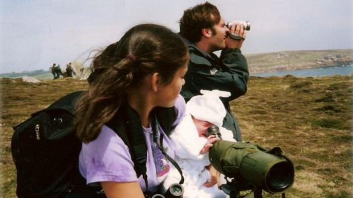 A woman holds a baby who is lookng through a telescope. A man stands in the background peering out through binoculars