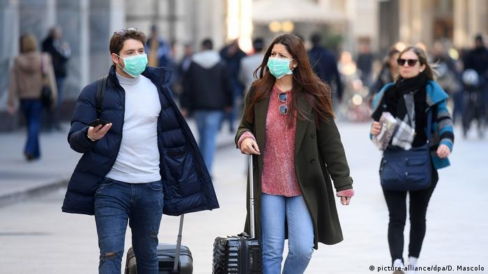 Turistas de máscara em Milão