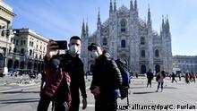 24.02.2020, Italien, Mailand: Touristen fotografieren sich mit Mundschutz vor der Kathedrale. Foto: Claudio Furlan/LaPresse via ZUMA Press/dpa +++ dpa-Bildfunk +++ |