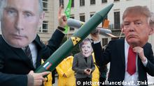 Protesters against nuclear weapons holding up images of Vladimir Putin and Donald Trump pointing rockets at each other — with Angela Merkel standing by (picture-alliance/dpa/P. Zinken)