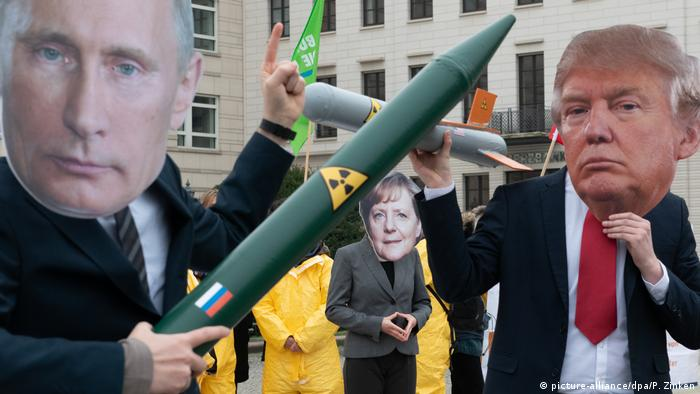 Three protesters in Berlin demonstrate against the abolition of the INF nuclear disarmament treaty. One is wearing a Vladimir Putin mask and holding a mock missile, another has a Trump mask and a missile with an American flag. In the middle of the pair stands someone with an Angela Merkel mask.