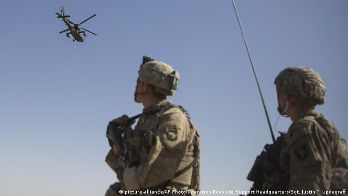 US soldiers looking at Apache helicopter