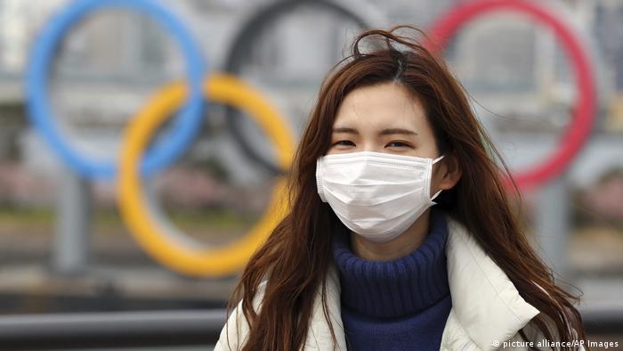 A woman wearing a mask walks near the Olympics' mark in Odaiba, Tokyo