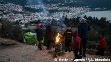 A family stands around a fire in the unofficial refugee camp of the Greek island of Samos on February 22, 2020. - The new conservative government wants to build one more camp on the island for up to 7,000 people, a plan which the local authority and community are rejecting outright. (Photo by ARIS MESSINIS / AFP) (Photo by ARIS MESSINIS/AFP via Getty Images)