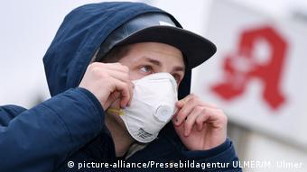 Молодой мужчина надевает респираторную маску