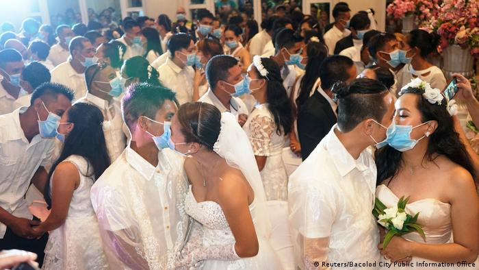 Filipino couples kiss with face masks in mass wedding.