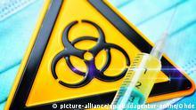 Symbolfoto Vorsichtsmaßnahmen Coronavirus | Spritze und Biogefährdungsschild auf Mundschutz