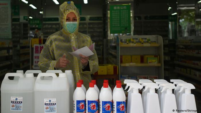 A salewoman in Wuhan with botttles of disinfectant
