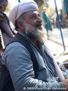 A local man smiles at a market in Khogyani