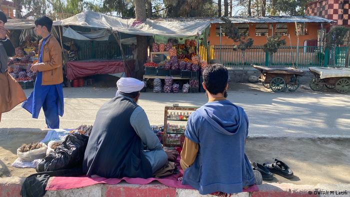 A perfume vendor at the Khogyani market jokes with local youth