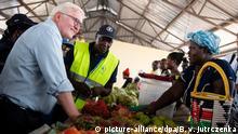 26.02.2020, Kenia, Kakuma: Bundespräsident Frank-Walter Steinmeier (l) besucht den Markt von Kalobeyei bei Kukuma, auf dem Flüchtlinge ihr selbstangebautes Gemüse verkaufen, und kauft sich Äpfel. Kakuma ist eines der größten Flüchtlingslager des Landes. Mehr als eine halbe Million geflüchteter Menschen aus über 30 Ländern leben derzeit in Kenia. Bundespräsident Steinmeier ist zu einem dreitägigen Staatsbesuch in Kenia. Foto: Bernd von Jutrczenka/dpa   Verwendung weltweit