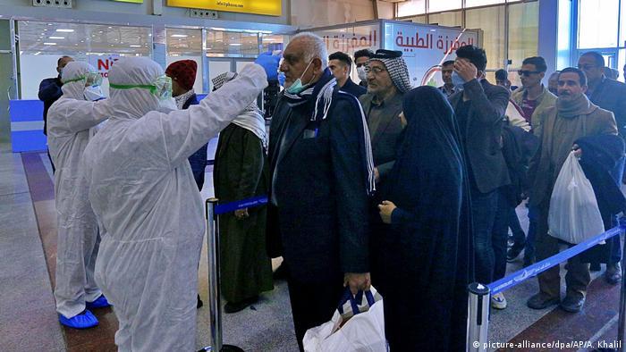 Irak Nadschaf | Coronavirus: Medizinisches Personal kontrolliert Passagiere (picture-alliance/dpa/AP/A. Khalil)