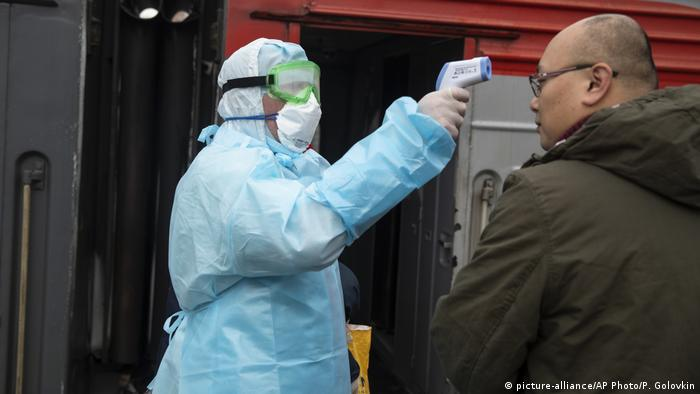Мужчина в защитном костюме и респираторной маске измеряет пассажиру с азиатской внешностью темпратуру в московском общественном транспорте