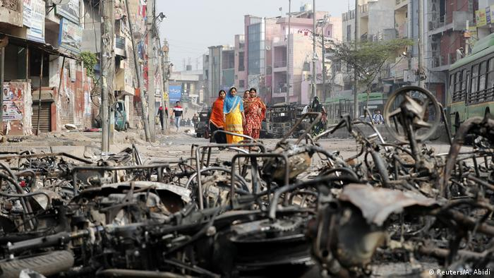 Women walk past charred vehicles in a riot affected area following clashes between people demonstrating for and against a new citizenship law in New Delhi, India, February 27, 2020