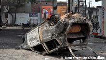 A burnt car lies overturned at a damaged fuel station after it was set on fire by a mob in a riot affected area after clashes erupted between people demonstrating for and against a new citizenship law in New Delhi, India, February 26, 2020. REUTERS/Rupak De Chowdhuri