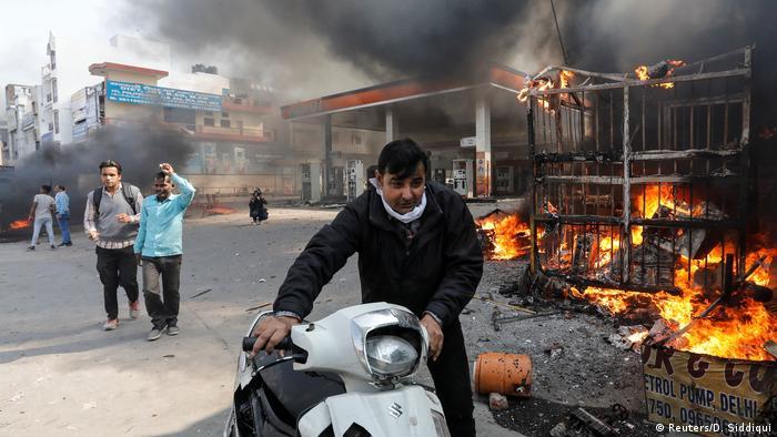A man walks past a burning gas station in New Delhi