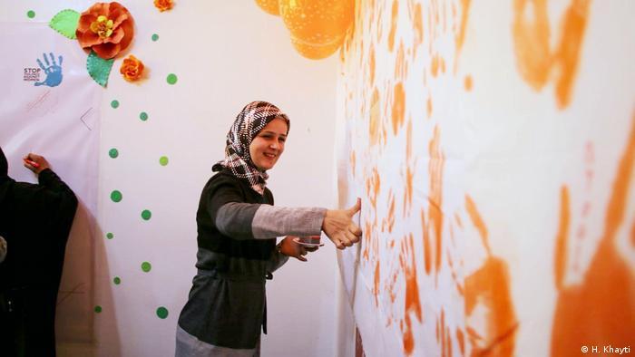 Huda Khayti decorates a wall with paint in Idlib