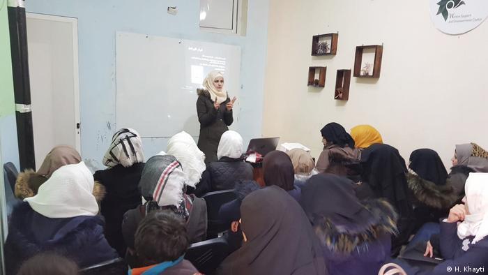 Huda Khayti speaks in front of a group of people