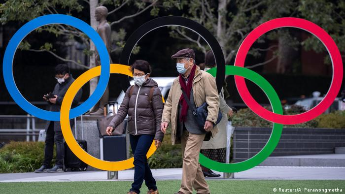 Прохожие в масках на фоне олимпийских колец в Токио