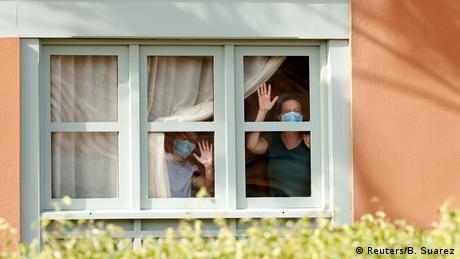 Gente con máscaras de respiración mirando a través de una ventana y saludando.