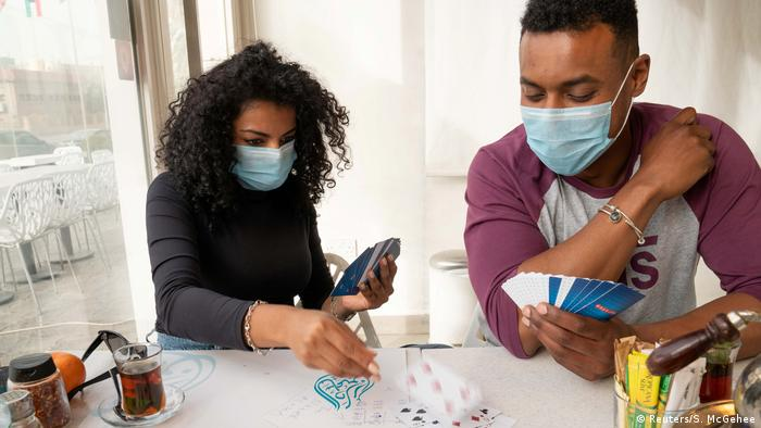 People wear protective masks while they play cards in a coffee shop in Salmiya, Kuwait on February 26.