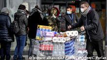 23.02.2020, Italien, Casalpusterlengo: Menschen tragen Atemschutzmasken und stehen vor einem Supermarkt in einer Schlange. Nach dem Tod zweier Menschen sind Teile des öffentlichen Lebens zum Erliegen gekommen. Kein europäisches Land hat mehr Infektionen mit dem Virus Sars-CoV-2 registriert als Italien. Foto: Claudio Furlan/LaPresse/AP/dpa +++ dpa-Bildfunk +++ |