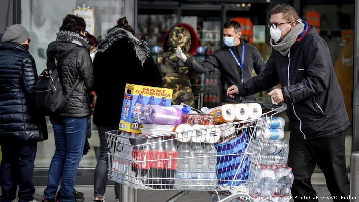 Мужчина с полной тележкой туалетной бумаги, бытовой химии и напитков - закупка из-за коронавируса
