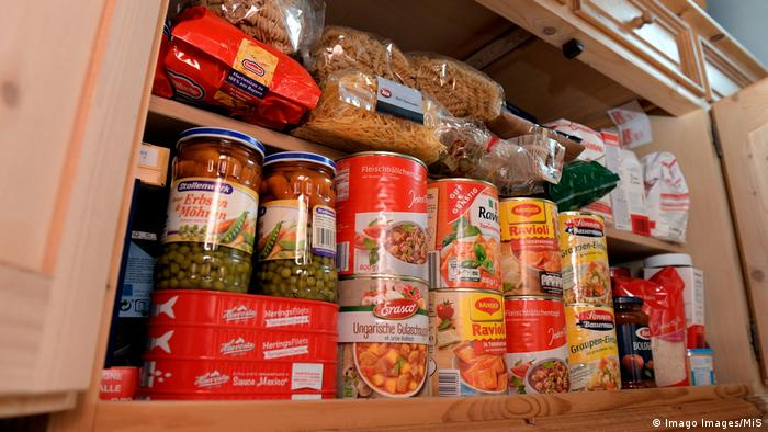 A kitchen cupboard filled with canned groceries