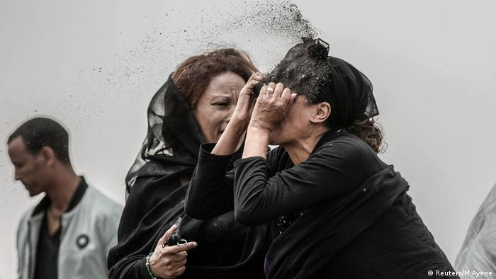 A relative of a victim of the crash of Ethiopian Airlines Flight ET302 throwing dirt in her face
