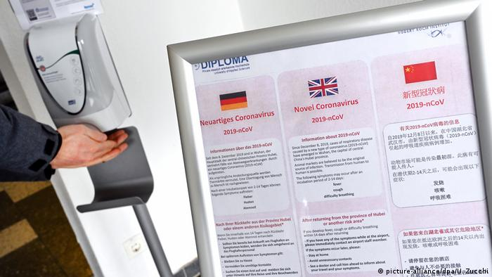 A person's hands under a disinfectant spray in Germany with coronavirus notices in German, English and Chinese