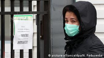 Женщина в защитной маске перед входом в инфекционную больницу в Минске