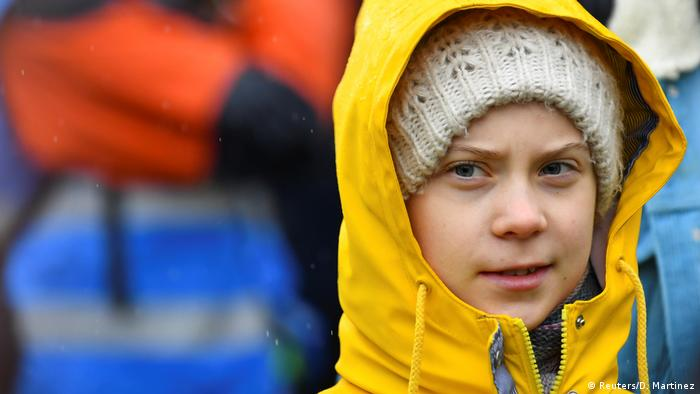 A closeup of Greta Thunberg in a yellow rain jacket