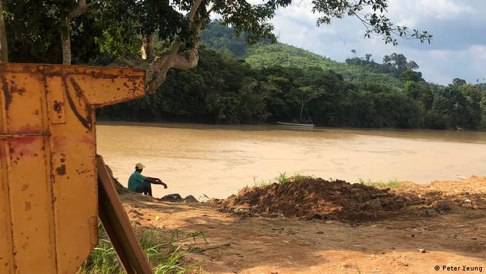 A man sits on the banks of a river in the Amazon. Mining equipment is visible in the foreground