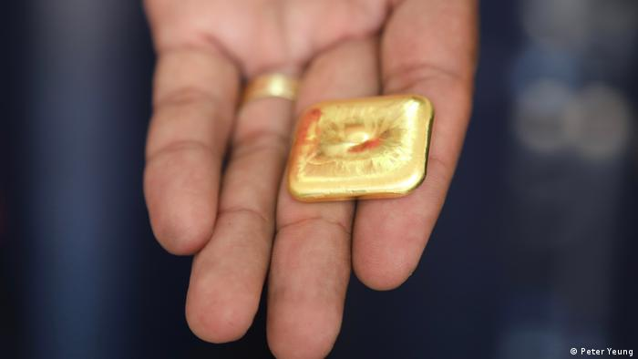 A close-up of a hand holding a nugget of gold
