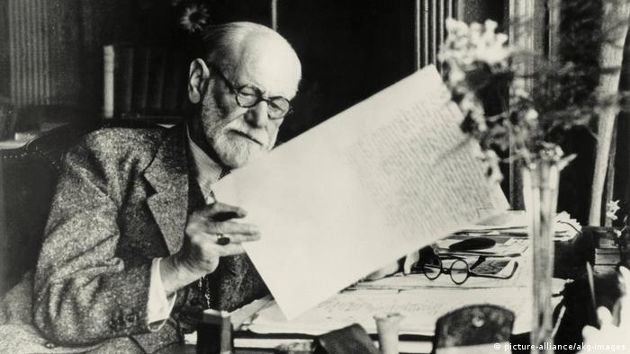 Sigmund Freud looking at a sheet of paper with writing on it (picture-alliance/akg-images)