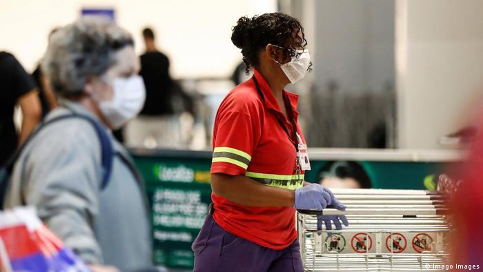 Funcionários e passageiros usam máscaras no aeroporto internacional de Guarulhos, em São Paulo