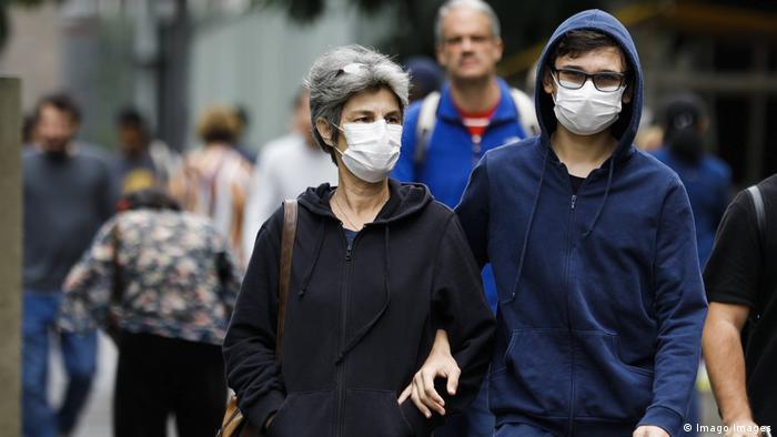 Mulher e homem com máscara caminham em São Paulo