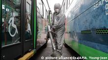 26.02.2020, Südkorea, Seoul: Ein Arbeiter in einem Schutzanzug und Mundschutz versprüht in einem Busdepot Desinfektionsmittel zwischen zwei Bussen als Schutzmaßnahme gegen die Verbreitung des Coronavirus. Foto: Ahn Young-Joon/AP/dpa +++ dpa-Bildfunk +++