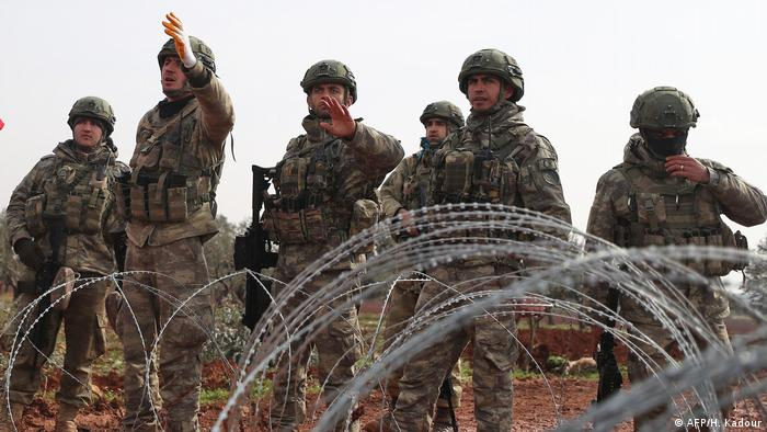 Turkish soldiers behind barbed wire in Idlib