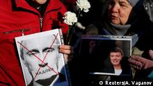 People hold photographs of Russian President Vladimir Putin and opposition politician Boris Nemtsov during a rally marking the 5th anniversary of Nemtsov's murder, in Saint Petersburg, Russia February 29, 2020. The inscription reads: Sick of. REUTERS/Anton Vaganov