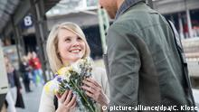 Mann holt Freundin mit Blumenstrauß ab