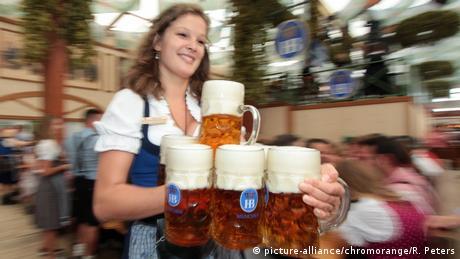 Kellnerin im Festzelt stemmt Maßkrüge Bier (picture-alliance/chromorange/R. Peters)