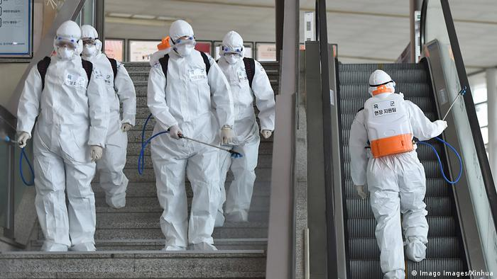 Staff disinfect a train station in Daegu, South Korea