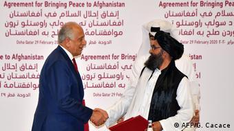 Спецпредставитель США по Афганистану Залмай Халилзад и заместитель лидера Талибана Абдулла Гани Барадар после подписания мирного соглашения в Дохе, февраль, 2020 год