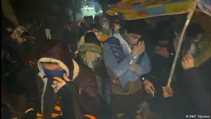 People shield their eyes from tear gas and smoke at night