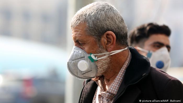 Homem usa máscara respiratória, com jovem também de máscara ao fundo