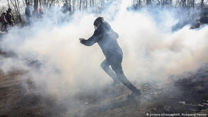 A migrant runs as Greek security forces intervene at the border between Turkey and Greece