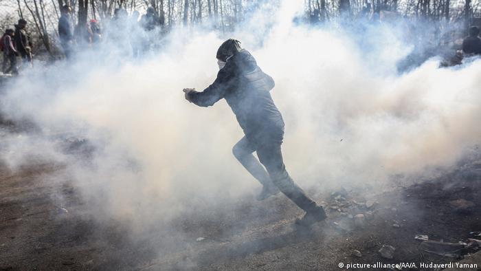 لاجئ يهرب من قنابل الغاز المسيل للدموع أطلقتها قوات حرس الحدود اليونانية