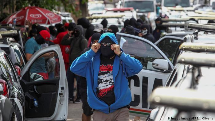 Homem com balaclava e casaco azul perto de carros da polícia